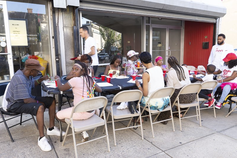 a group of attendees sit outside Abstract gallery and paint canvases