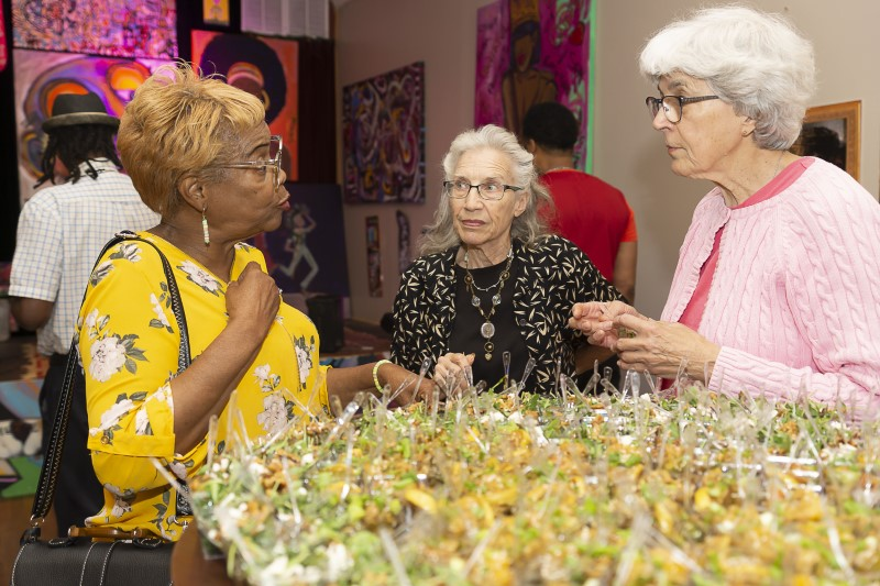 three women talk over appetizers in MJ Freed gallery space