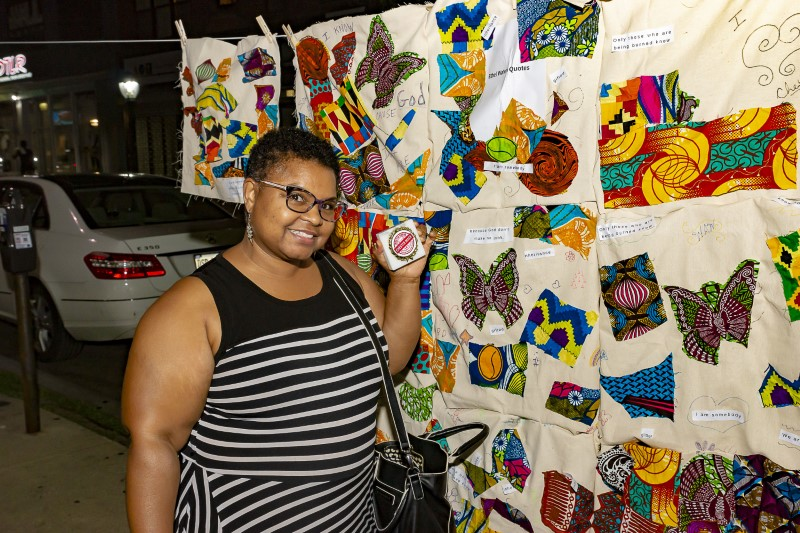 Connie poses with her Chester Made plaque in front of the colorful quilt