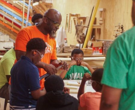 Najee and scouts continuing to work on their project in the Makerspace
