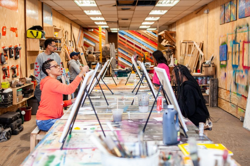 a group paints on easels set up in the Makerspace